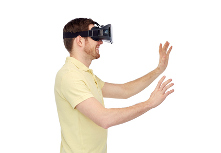 modified: 3d technology, virtual reality, entertainment and people concept - happy young man with virtual reality headset or 3d glasses playing game Stock Photo