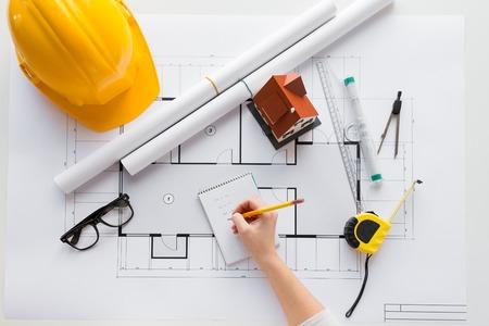 negocio, arquitectura, construcción, construcción y concepto de la gente - cerca de la mano del arquitecto con el modelo de arquitectura y herramientas que escribe al cuaderno