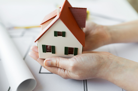 architecture model: architecture, building, construction, real estate and people concept - close up of architect hands holding living house model above blueprint on table Stock Photo