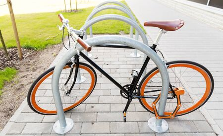 transport, storage, security and safety concept - close up of fixed gear bicycle locked at street parking outdoors Stock Photo