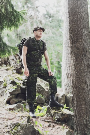 hombre con sombrero: war, hiking, army and people concept - young soldier or ranger with backpack walking in forest