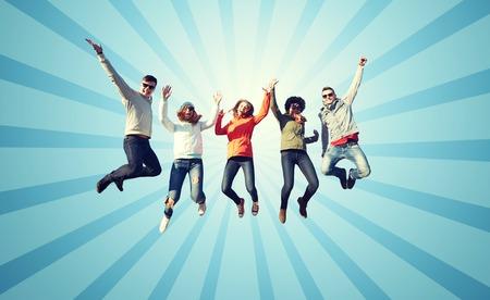 personas saltando: las personas, la libertad, la felicidad y el concepto de adolescentes - grupo de amigos felices con gafas de sol salto de altura sobre fondo azul los rayos de ráfaga Foto de archivo