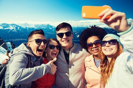 people, travel, tourism, friendship and technology concept - group of happy teenage friends taking selfie with smartphone and showing thumbs up over alps mountains in austria background