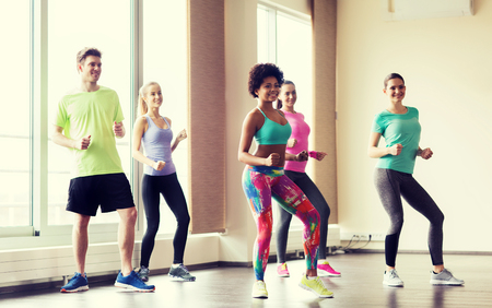 dance studio: fitness, sport, dance and lifestyle concept - group of smiling people with coach dancing in gym or studio Stock Photo