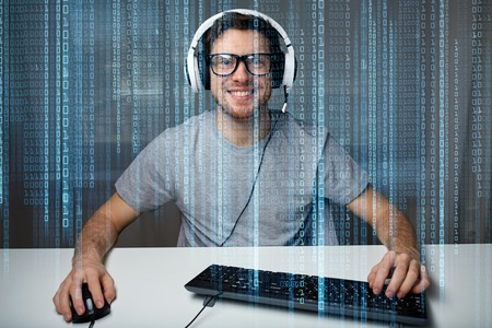 lets: technology, gaming, entertainment, lets play and people concept - happy smiling young man in eyeglasses with headset playing computer game at home and streaming playthrough or walkthrough video