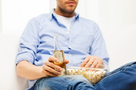 unhealthy living: food, junk-food, unhealthy eating and people concept - close up of man with popcorn and beer bottle at home
