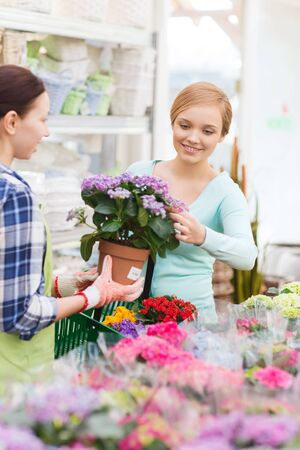 people, gardening, shopping, sale and consumerism concept - happy gardener helping woman with choosing flowers in greenhouse or shop