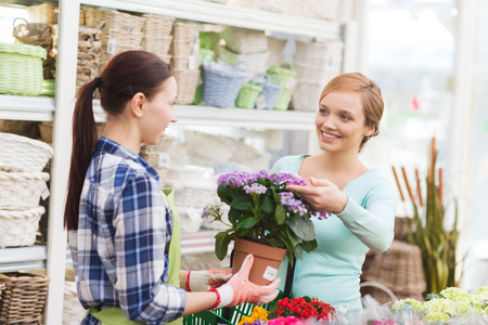people, gardening, shopping, sale and consumerism concept - happy gardener helping woman with choosing flowers in greenhouse Stock Photo