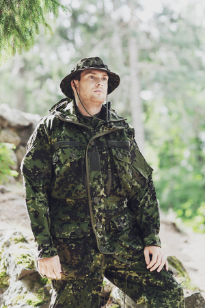 war, army and people concept - young soldier or ranger wearing military uniform in forest Stock Photo