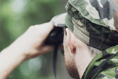 cazador: la caza, la guerra, el ejército y el pueblo concepto - cerca de la joven soldado, guardabosques o cazador con binoculares observando el bosque Foto de archivo