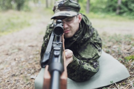 hunting, war, army and people concept - close up of young soldier, ranger or hunter with gun in forest Stock Photo
