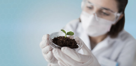 biotech: science, biology, ecology, research and people concept - close up of young female scientist wearing protective mask holding petri dish with plant and soil sample over blue background