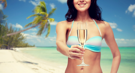 wine background: people, summer holidays, travel, celebration and drinks concept - happy young woman in bikini swimsuit drinking champagne at party over tropical beach background