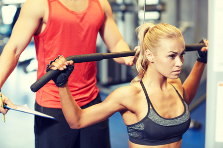 flexing: sport, fitness, teamwork and people concept - young woman and personal trainer flexing muscles on gym machine