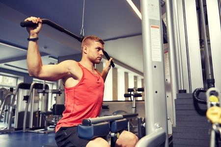 スポーツ、フィットネス、ボディービル、ライフ スタイル、人々 の概念 - 運動とジムでケーブル マシンでの筋肉がうごめく男