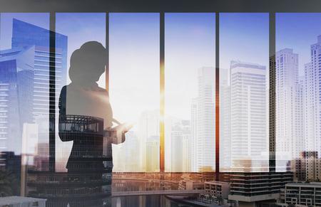 ビジネスや人々 のコンセプト - 事務所ウィンドウ背景二重露出オフィスと都市背景の上にタブレット pc を持つ女性のシルエット