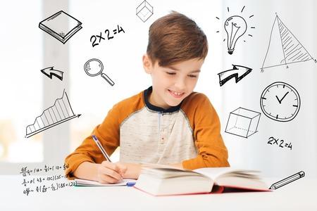 Bildung, Kindheit, Menschen, Hausaufgaben und Schulkonzept - Schüler Junge mit Buch schriftlich Notebook zu Hause über mathematische Kritzeleien lächelnd