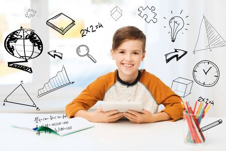 school boy: leisure, children, education, technology and people concept - smiling boy with tablet pc computer and notebook at home over mathematical doodles Stock Photo