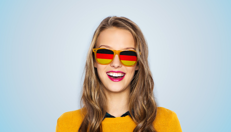 german: people, patriotism and nationality  concept - happy young woman or teen girl face in sunglasses with german flags over blue background
