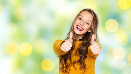 green clothes: people, gesture, style and fashion concept - happy young woman or teen girl in casual clothes showing thumbs up over summer green lights background Stock Photo