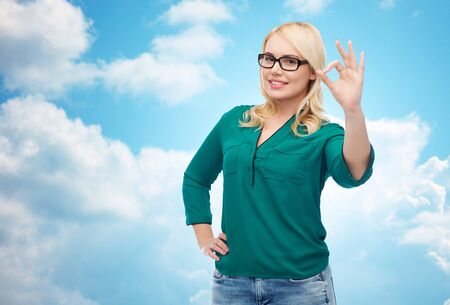 overweight students: vision, optics, education, gesture and people concept - smiling young woman with eyeglasses showing ok over blue sky and clouds background