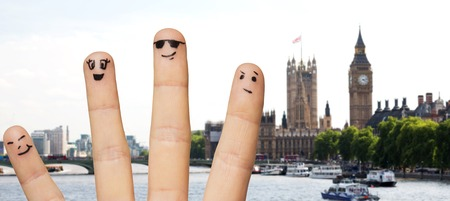 four people: travel, tourism, family, people and body parts concept - close up of four fingers with smiley faces over london city background Stock Photo