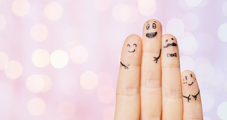 four people: gesture, family, people and body parts concept - close up of four fingers with smiley faces over pink holidays lights background