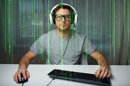 cyber terrorism: technology, gaming, entertainment, lets play and people concept - young man in headset and eyeglasses with pc computer playing game at home and streaming playthrough or walkthrough video