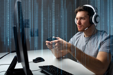 technology, gaming, entertainment, lets play and people concept - young man in headset with controller gamepad playing computer game at home and streaming playthrough or walkthrough video