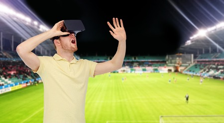 entertainment background: 3d technology, virtual reality, sport, entertainment and people concept - happy young man with virtual reality headset or 3d glasses playing game over football field on stadium background
