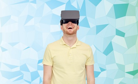 mediated: 3d technology, virtual reality, entertainment and people concept - happy young man with virtual reality headset or 3d glasses playing game over low poly background