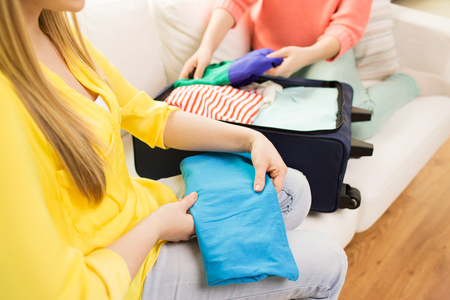 trip, vacation, luggage and people concept - close up of young woman or teenage girl packing clothes into travel bag