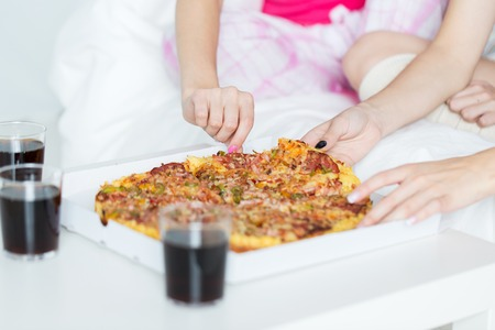 nightwear: friendship, people, pajama party and junk food concept - close up of friends or teenage girls eating pizza at home