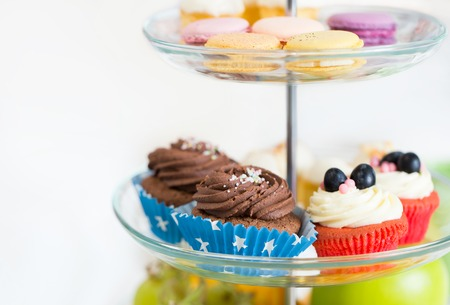 dessert stand: unhealthy eating, sweets, dessert, baking and junk food concept - close up of cake stand with cupcakes and cookies Stock Photo