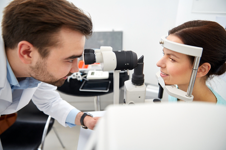 health care, medicine, people, eyesight and technology concept - optometrist with non contact tonometer checking patient intraocular pressure at eye clinic or optics store Zdjęcie Seryjne