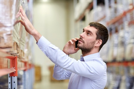 wholesale: wholesale, logistic, business, export and people concept - serious businessman calling on smartphone at warehouse