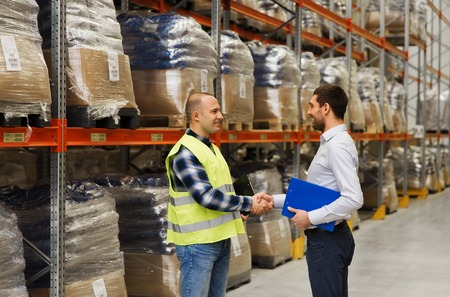 deal: wholesale, logistic, people and export concept - manual worker and businessmen with clipboard shaking hands and making deal at warehouse