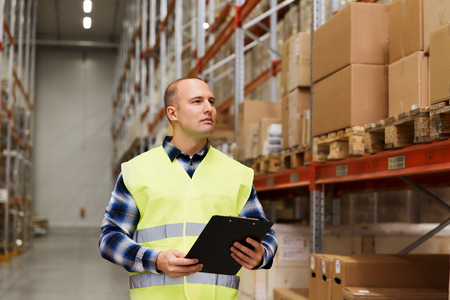 merchandise: wholesale, logistic, people and export concept - man with clipboard in reflective safety vest at warehouse