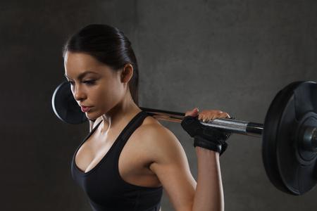 pesas: deporte, fitness, culturismo, levantamiento de pesas y el concepto de la gente - mujer joven con la barra flexionando los músculos en el gimnasio Foto de archivo
