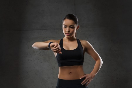 sport woman: sport, fitness, technology and people concept - young woman with heart-rate watch in gym