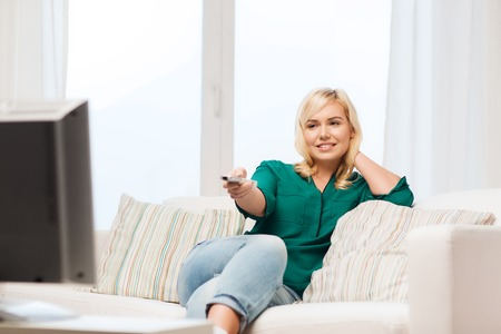 changing channel: television, leisure and people concept - smiling woman sitting on couch with remote control and watching tv at home Stock Photo