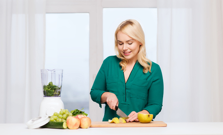 woman knife: healthy eating, cooking, vegetarian food, diet and people concept - smiling young woman with blender and knife chopping fruits and vegetables on cutting board at home Stock Photo