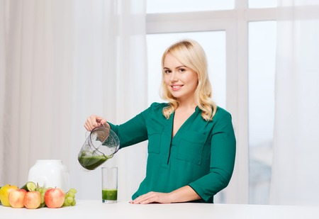 green vegetable: healthy eating, cooking, vegetarian food, diet and people concept - smiling young woman with blender shaker jug pouring green vegetable smoothie or juice into glass at home kitchen Stock Photo