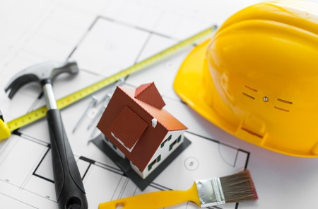 close up of living house model on blueprint with repair tools