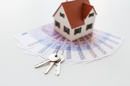housing prices: close up of home model, money and house keys Stock Photo
