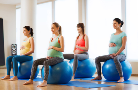 group of happy pregnant women exercising on ball in gym
