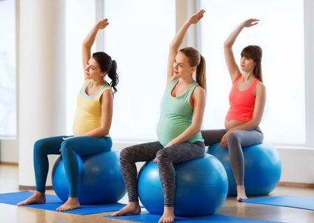 ジムにボール運動幸せな妊娠中の女性のグループ