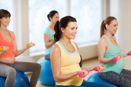 fitball: group of happy pregnant women with dumbbells exercising on ball in gym