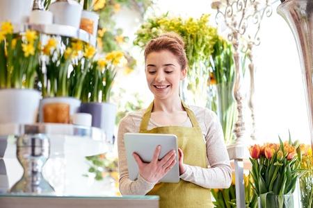 feliz mujer de floristería sonriendo con ordenador Tablet PC en la tienda de flores Foto de archivo