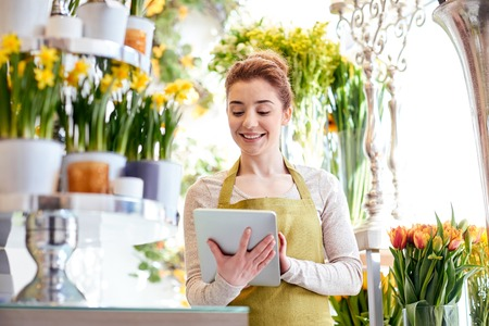 happy smiling florist woman with tablet pc computer at flower shop
